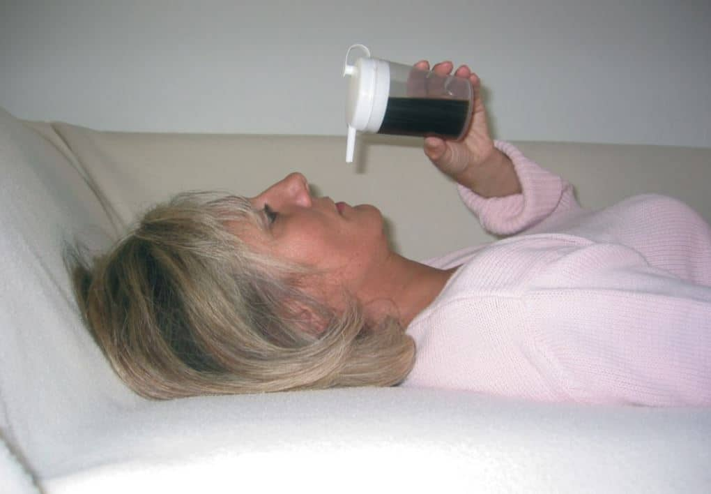 A woman laying down using a non spill drinking cup